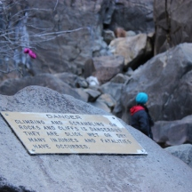A sign warns visitors to be careful while climbing rocks around the falls.